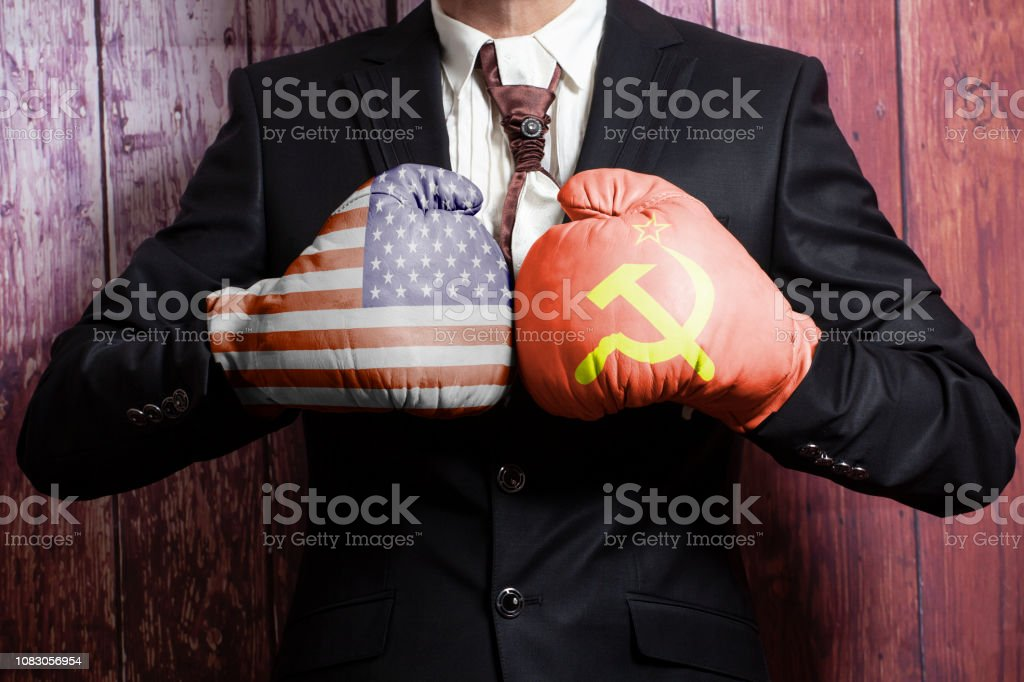 Businessman in boxing gloves with USA and USSR flags. USA vs. USSR concept stock photo