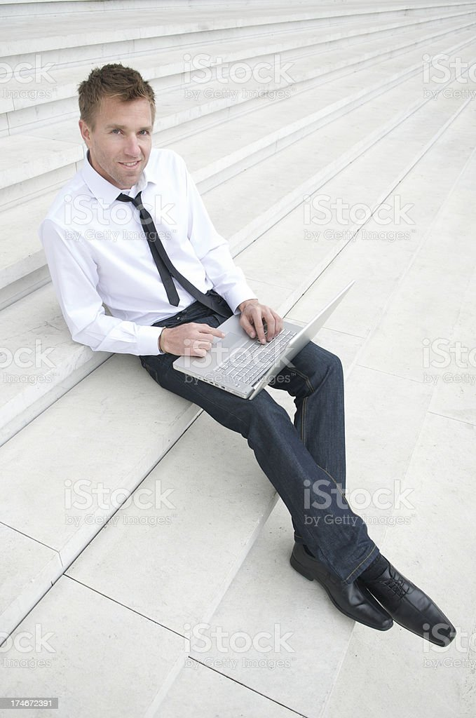Businessman in Business Casual Sits Typing on Laptop royalty-free stock photo
