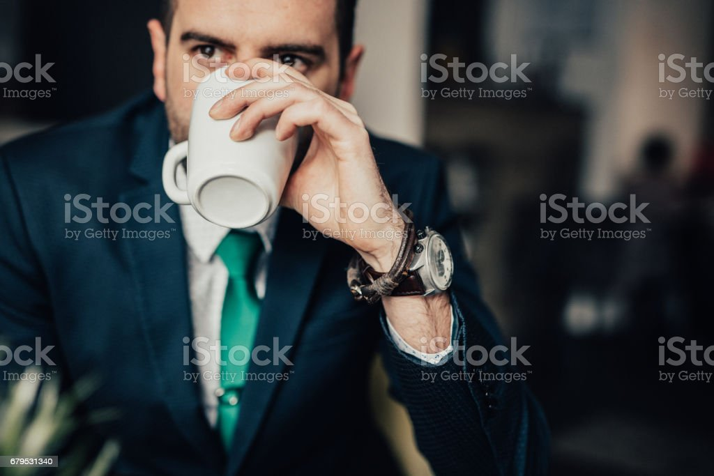 Businessman in cafe drinking tea from a mug royalty-free stock photo