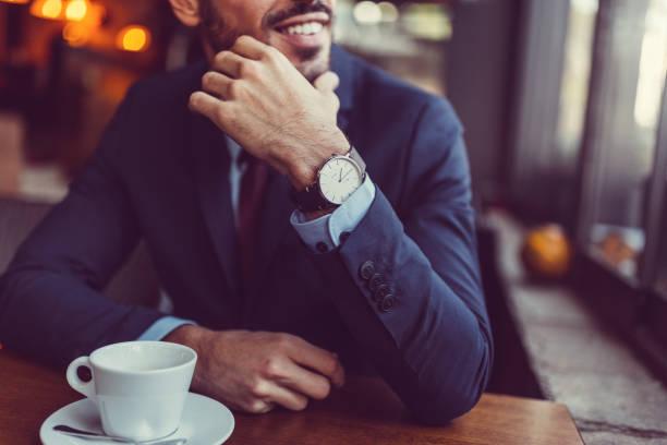empresario de café mirando por la ventana - reloj de pulsera fotografías e imágenes de stock
