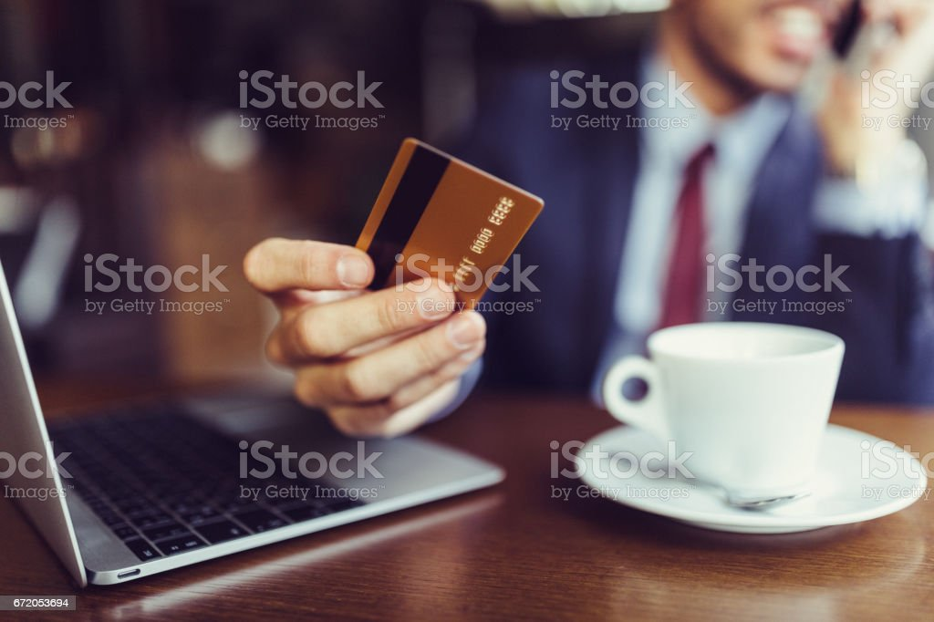 Businessman in cafe using credit card for online shopping stock photo