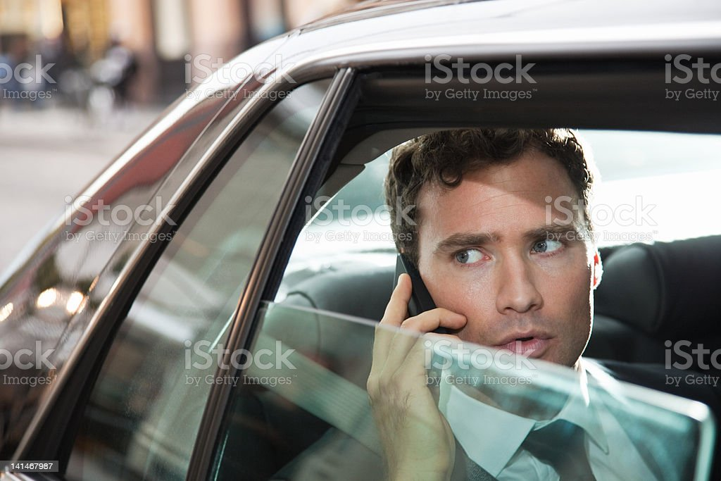 Businessman in car on cellphone stock photo