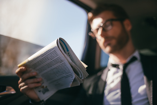 Businessman in car reading news paper