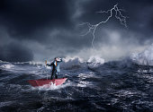 Businessman in the umbrella sails in storm in the night
