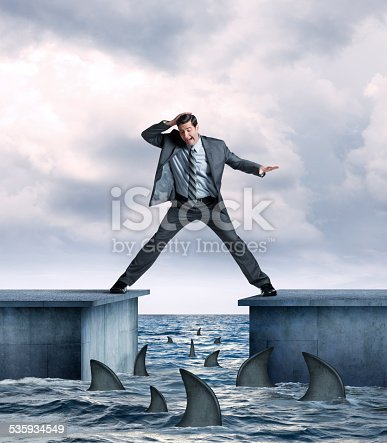 A businessman straddling two piers  tries not to fall into shark infested  ocean waters below.  Several sharks are circling the pier as the businessman's legs are stretched as far as they can go as he balances himself.  His hand is on top of his head as he looks down at the sharks below in fear.
