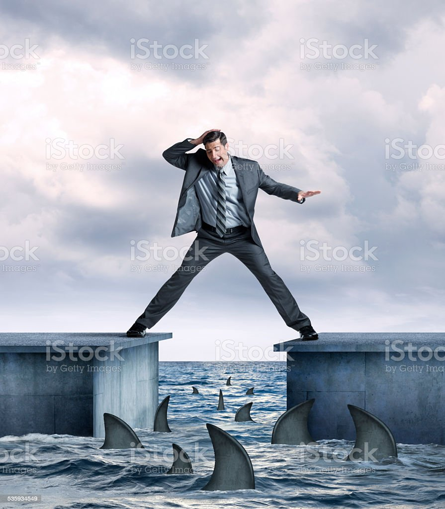 Businessman In Danger Of Falling Into Shark Infested Waters stock photo