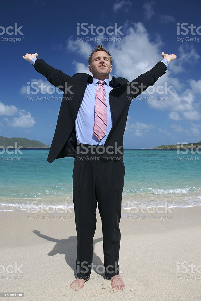 Businessman in Dark Suit Stretches on Tropical Beach stock photo