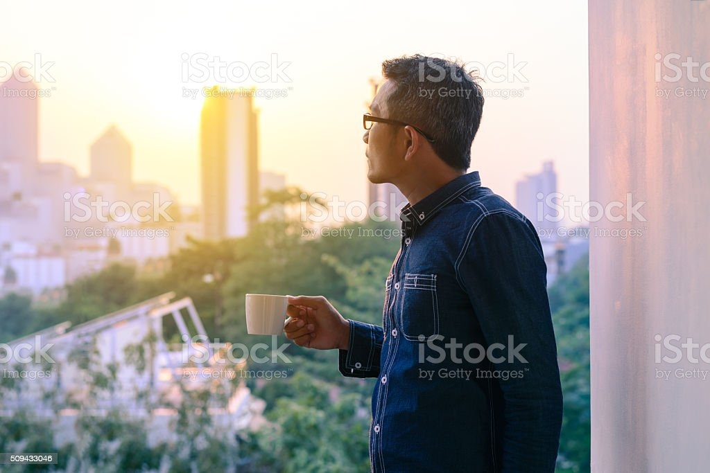 Businessman in denim jacket and glasses drinking hot coffee. stock photo