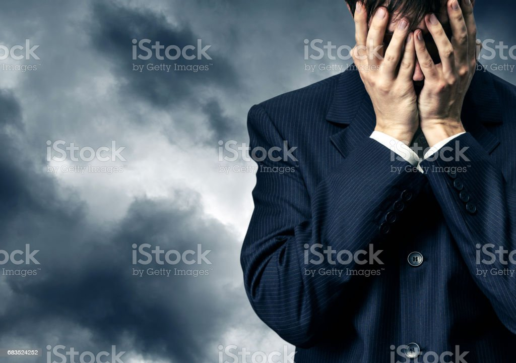 Businessman in despair on stormy sky stock photo