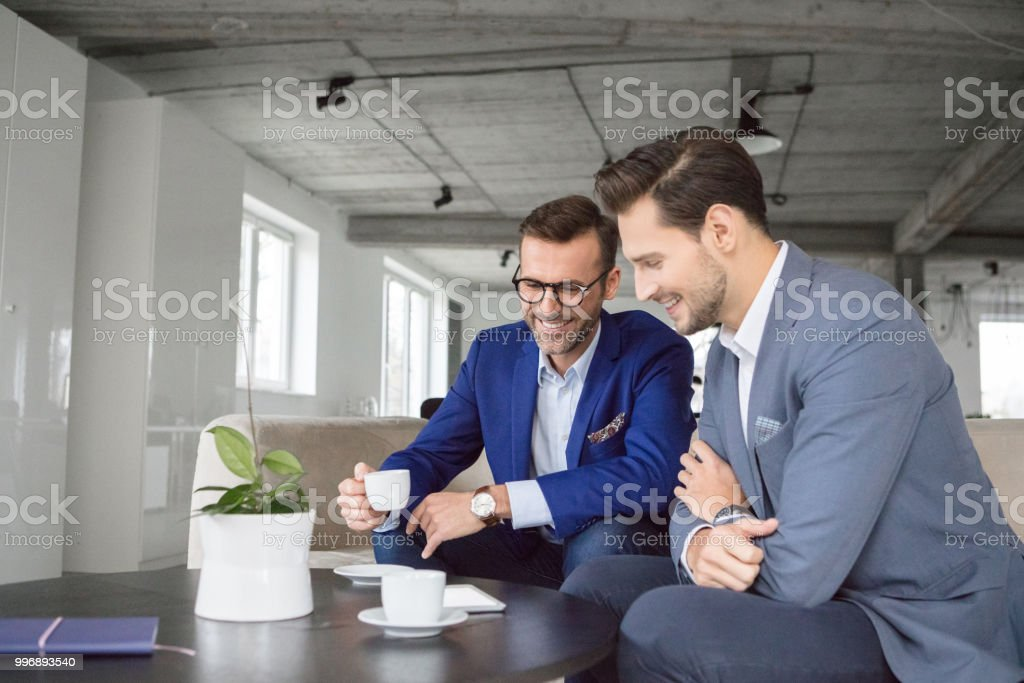 Businessman in discussion over a cup of coffee Two business men sitting at office lounge having coffee and having discussion Adult Stock Photo
