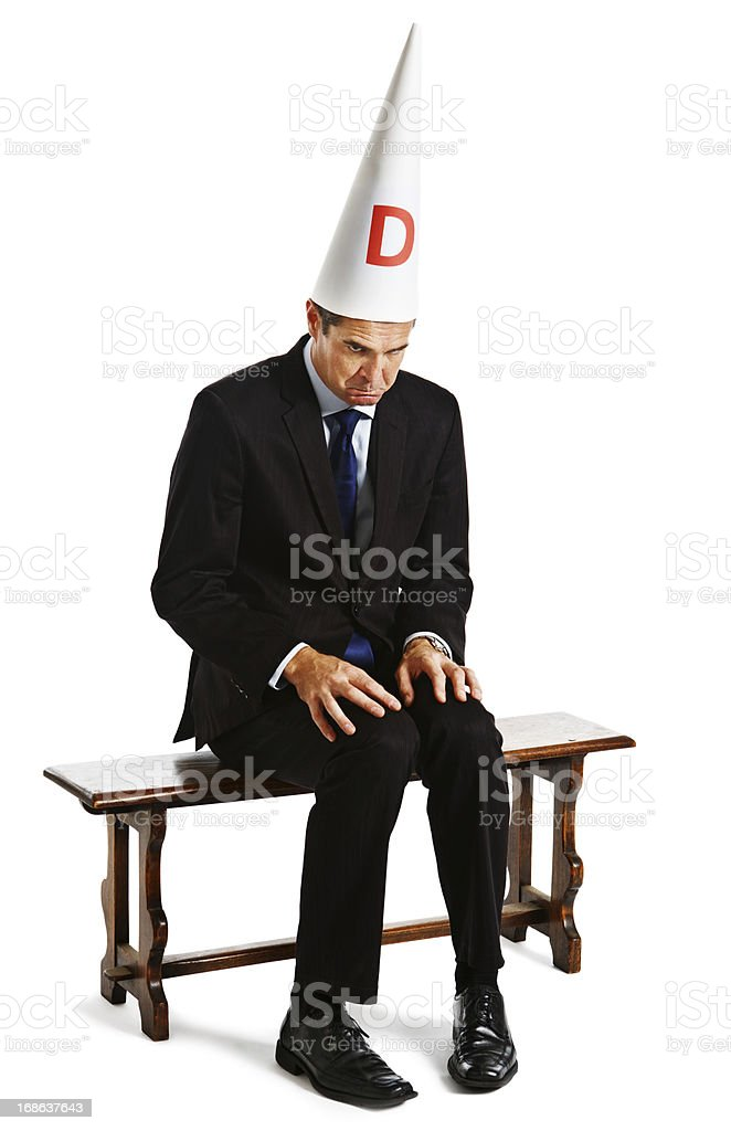 Businessman in dunce cap being punished sitting on naughty chair stock photo
