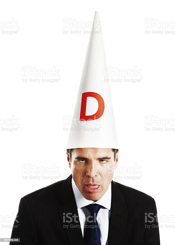 Businessman in dunce cap looking really dumb stock photo