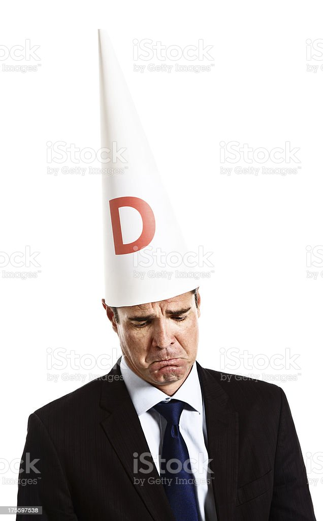 Businessman in dunce cap looks down ashamed and embarrassed royalty-free stock photo
