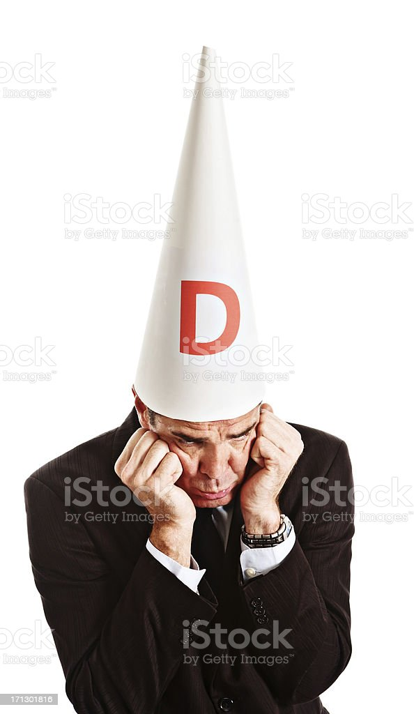Businessman in dunce cap looks embarassed grumpy and resentful stock photo