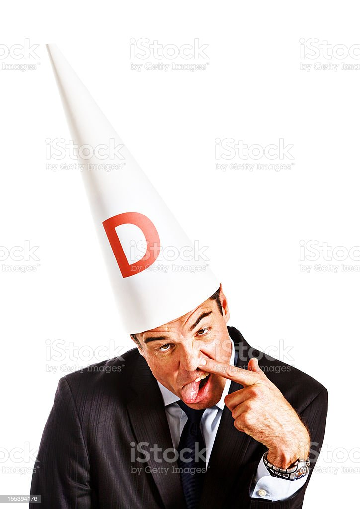 Businessman in dunce cap makes stupid face: work is insane! stock photo