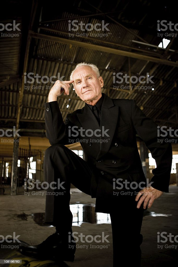 Businessman in empty warehouse with barrel Man in a business suit in a warehouse with his foot on a barrel of toxic waste looking at camera. Active Seniors Stock Photo