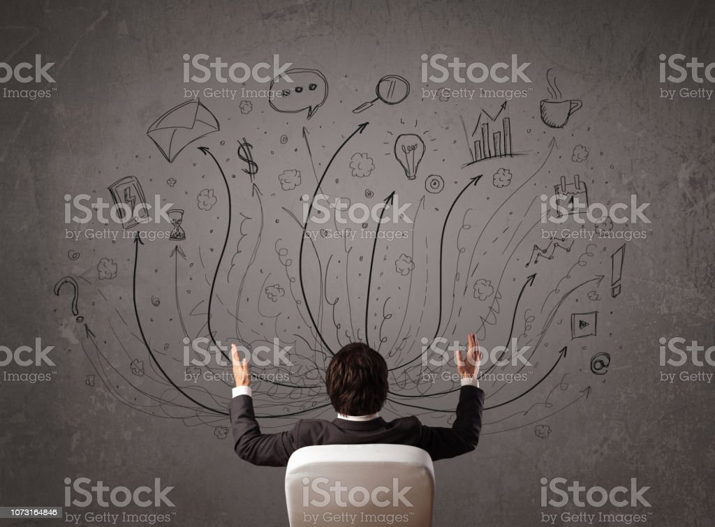 Businessman in front of a chalkboard deciding with arrows and signs - fotografia de stock