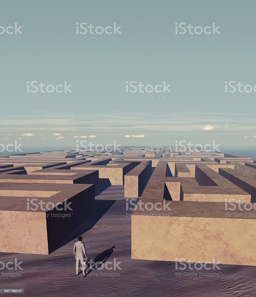 Businessman in front of a stone labyrinth stock photo
