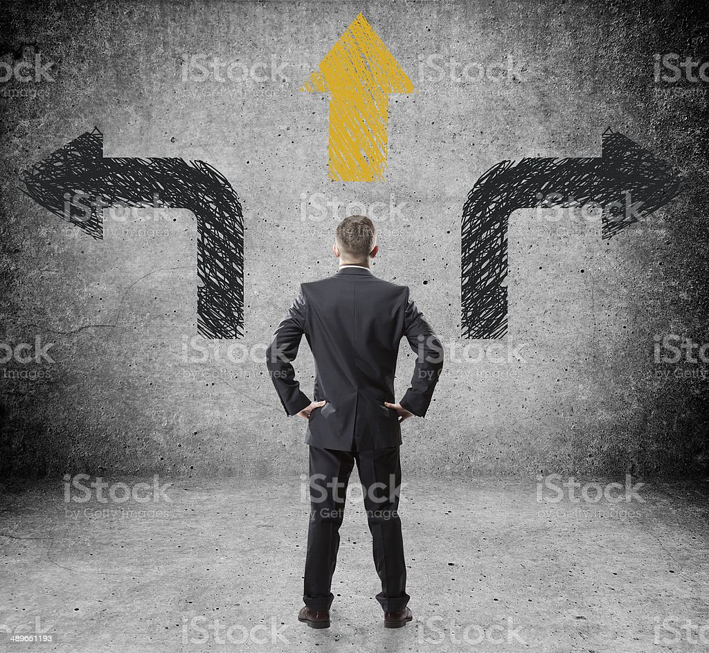 Businessman in front of a wall with arrows stock photo