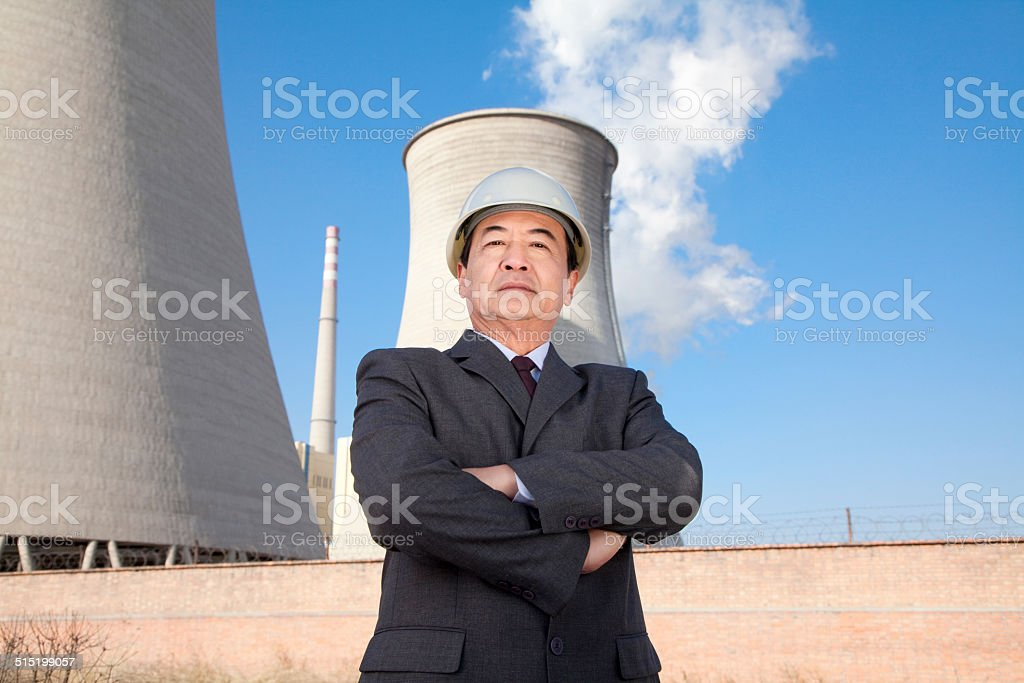 Businessman in front of cooling tower stock photo