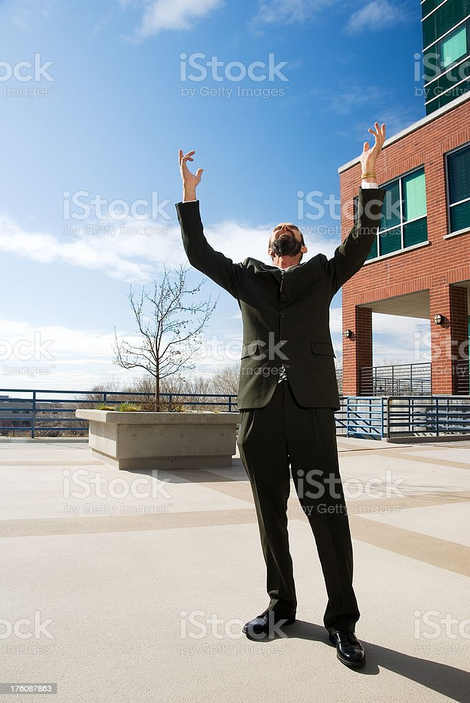 Businessman in front of the office building raising his arms stock photo