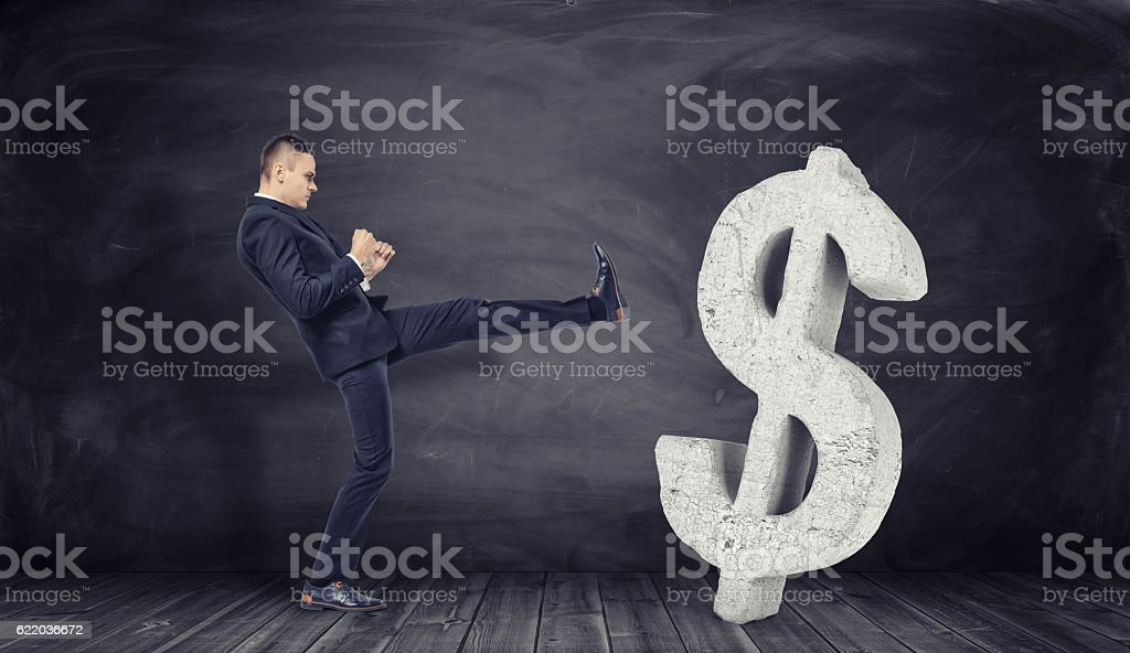 Businessman in full growth kicks off huge concrete dollar sign stock photo