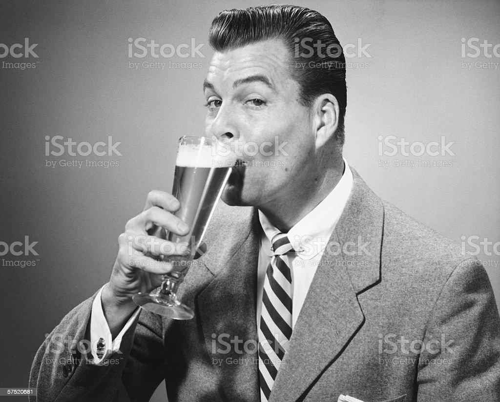 Businessman in full suit drinking beer in studio, (B&W), portrait stock photo