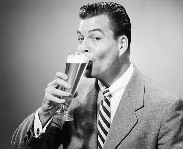 Businessman in full suit drinking beer in studio, (B&W), portrait stock photo
