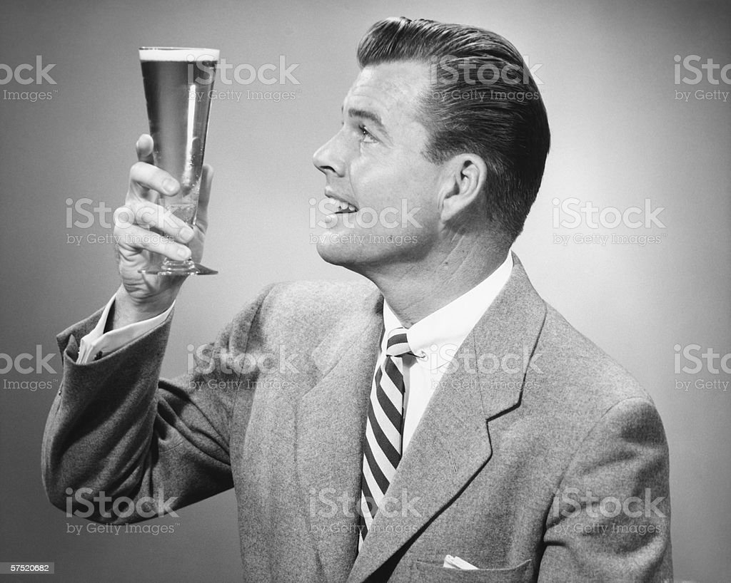 Businessman in full suit in studio holding glass of beer, (B&W) royalty-free stock photo