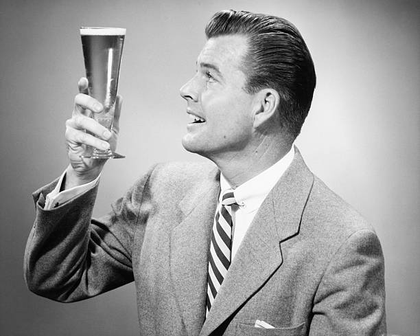 Businessman in full suit in studio holding glass of beer, (B&W) stock photo