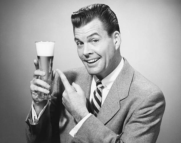 Businessman in full suit in studio pointing at glass of beer, (B&W), portrait stock photo