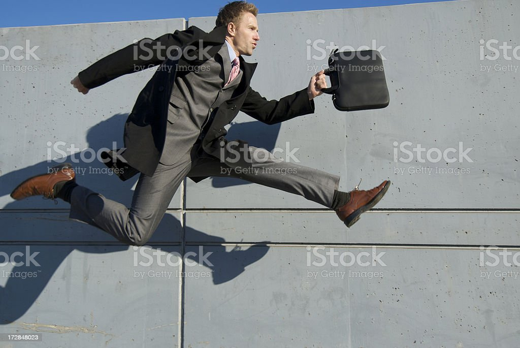 Businessman in Full Suit Jumping Outdoors Gray Wall Background stock photo