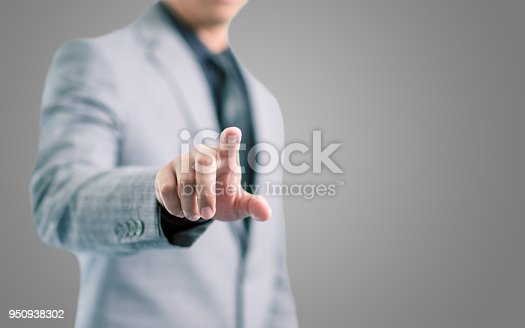 istock Businessman in gray suit is pointing his finger to touch the screen concept 950938302