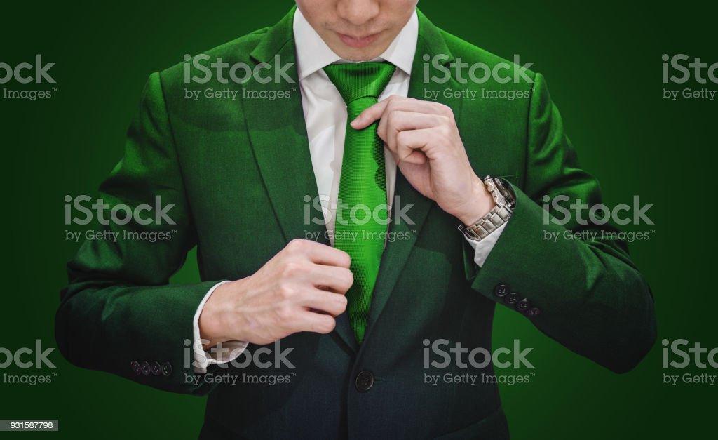Businessman in green suit tying green necktie stock photo