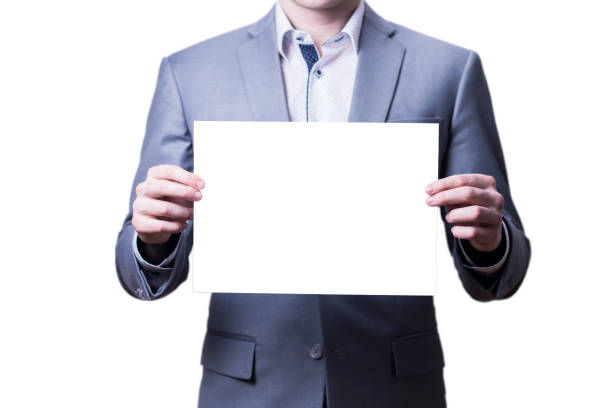 Businessman in grey suit holding blank paper on white background. stock photo