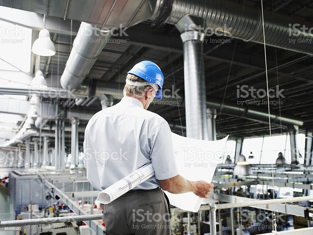 Businessman in hard-hat looking at blueprints 免版稅 stock photo