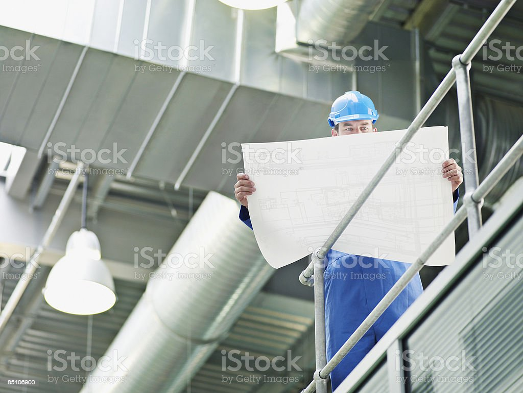 Businessman in hard-hat looking at blueprints royalty-free stock photo