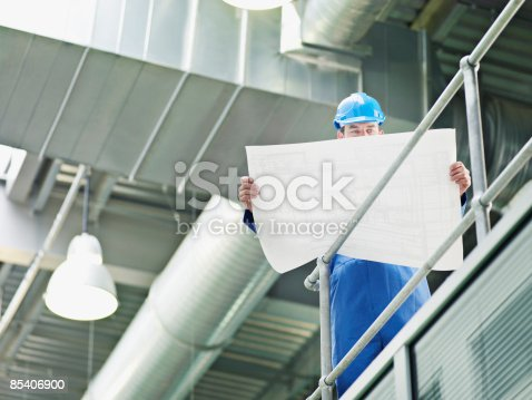 istock Businessman in hard-hat looking at blueprints 85406900