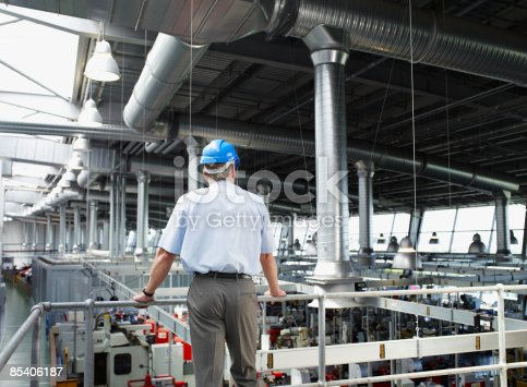 istock Businessman in hard-hat looking at factory floor 85406187