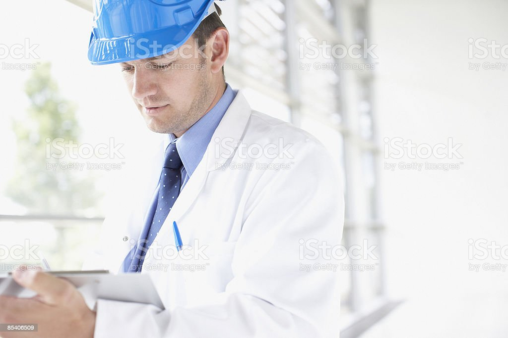 Businessman in hard-hat writing on clipboard royalty-free stock photo
