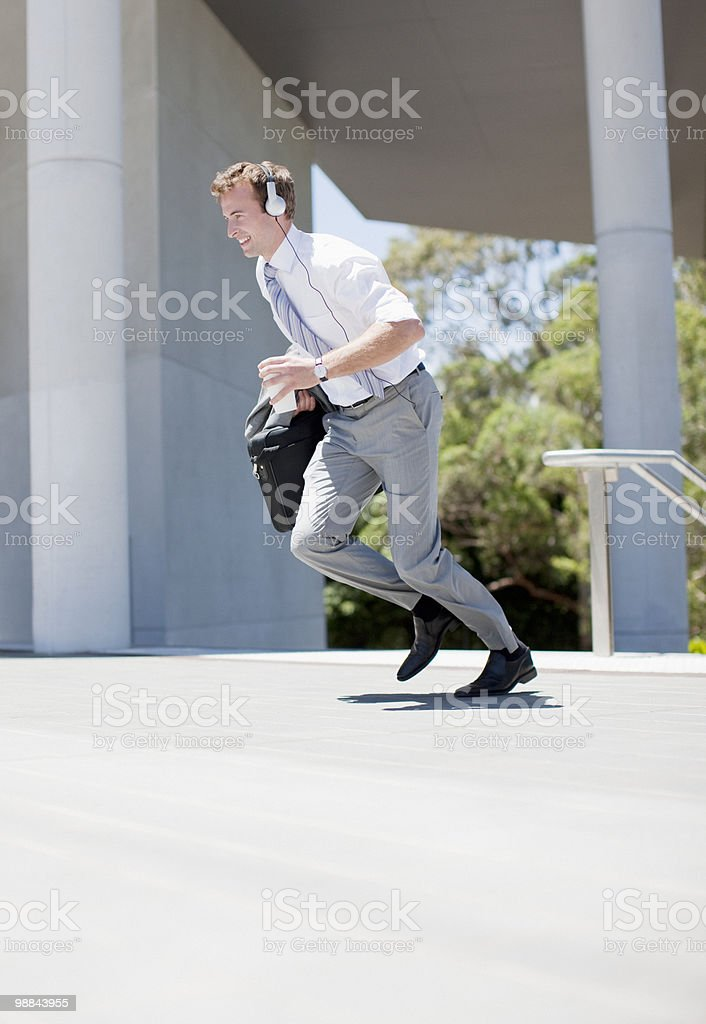 Businessman in headphones running outdoors royalty-free stock photo