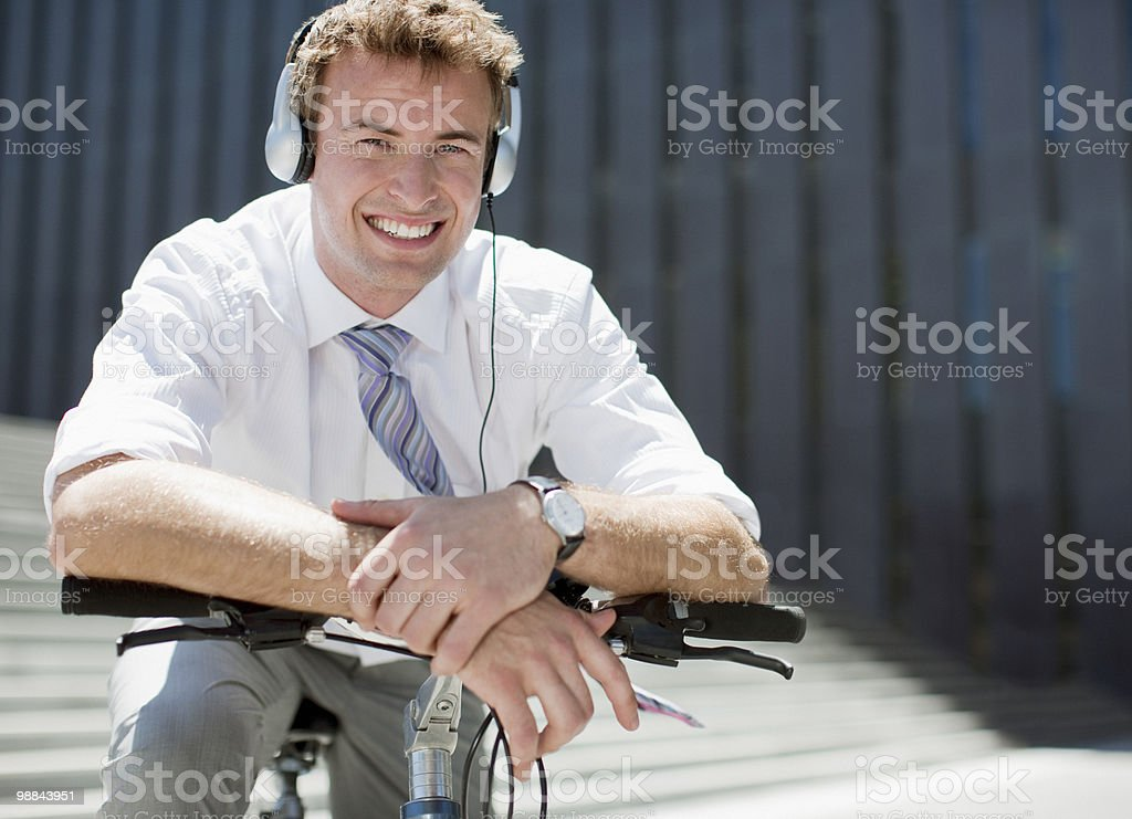 Businessman in headphones sitting on bicycle 免版稅 stock photo