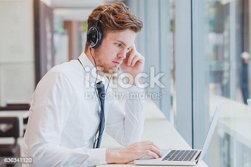 istock businessman in headphones working with laptop 636341120
