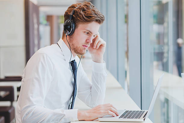 businessman in headphones working with laptop stock photo