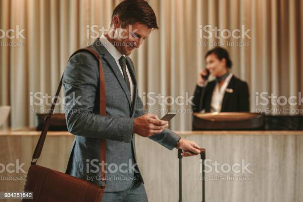 Businessman in hotel hallway with cellphone and luggage picture id934251842?b=1&k=6&m=934251842&s=612x612&h=jysikylbbowq6beke 000tvxercwsckmkbstm9a6pww=