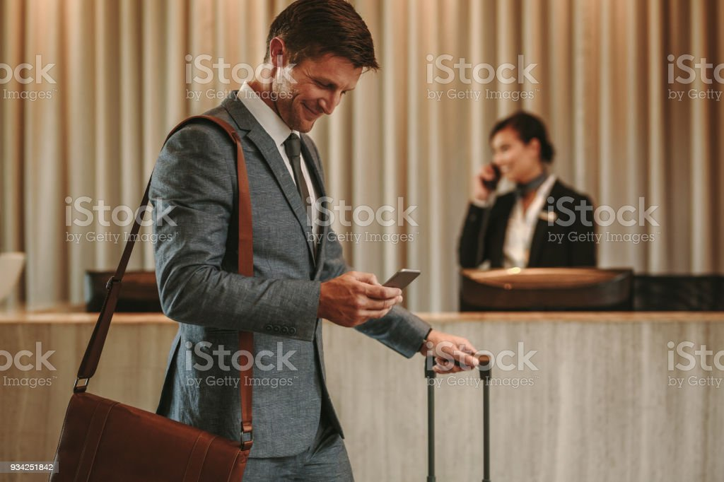 Businessman in hotel hallway with cellphone and luggage stock photo