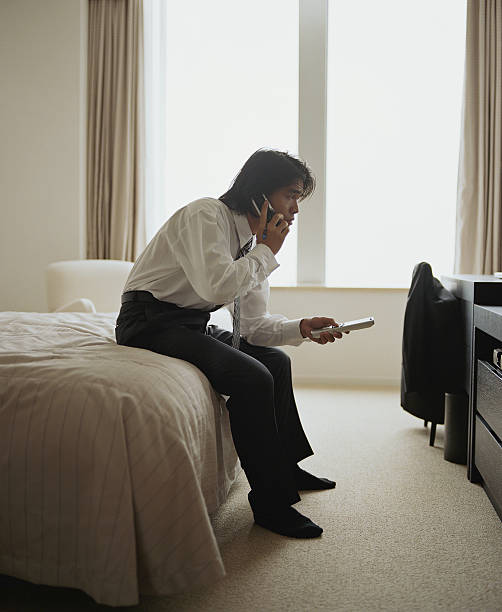 Businessman in hotel room, talking on cell phone and using remote stock photo