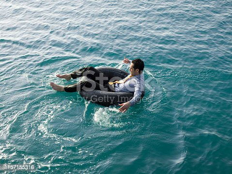 Businessman in inner tube at sea