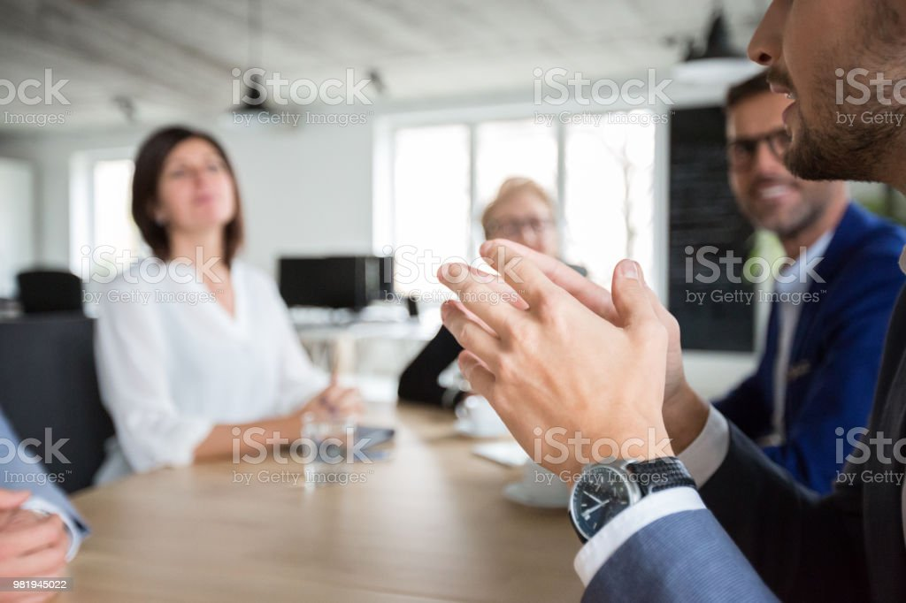 Businessman in meeting with colleagues in office Young businessman sharing his ideas with colleagues in conference room meeting. Focus on hands of businessman talking with coworkers. Adult Stock Photo
