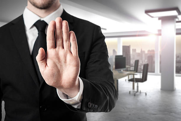 businessman in modern office hand stop gesture - disbarment stock pictures, royalty-free photos & images
